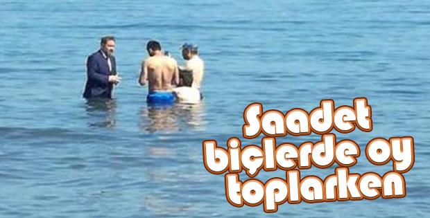 Milletvekili adayı takım elbise ile denize girdi