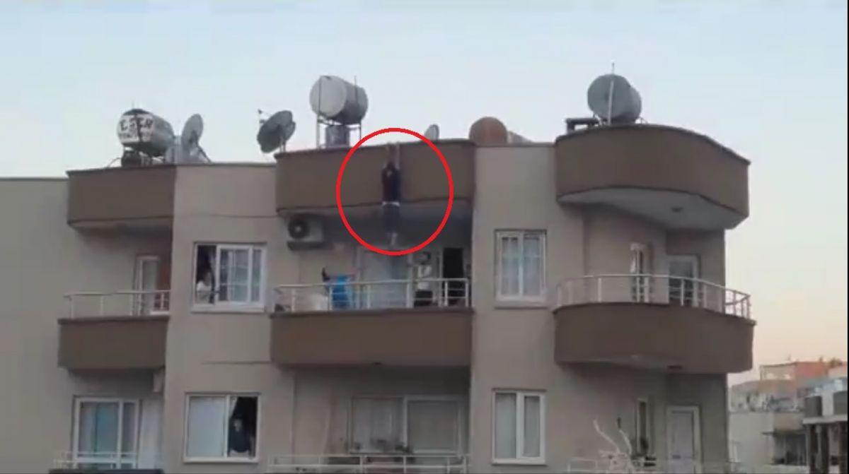 Mersin de binanın çatısından sarkan kişi yürekleri ağza getirdi #1