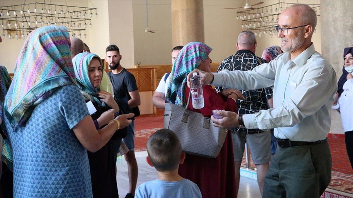 İzmir de camiyi ziyeret eden turistlere 15 dildeki Kur an-ı Kerim kitapçıklarını hediye ediyor #4