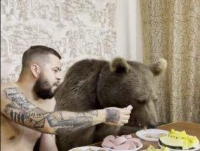 Rusya'da ayısıyla birlikte yemek yiyerek, çizgi film izledi